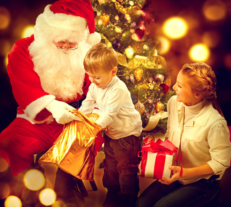 Santa Claus giving Christmas gifts to children. Christmas holiday scene stock images
