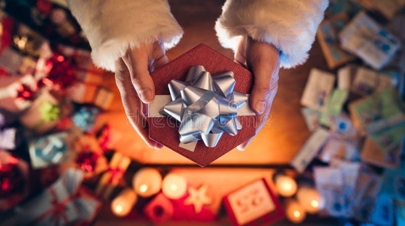 Santa Claus Giving ein Weihnachtsgeschenk lizenzfreie stockfotos