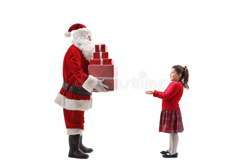 Santa Claus giving a pile of Christmas presents to a happy little girl stock images