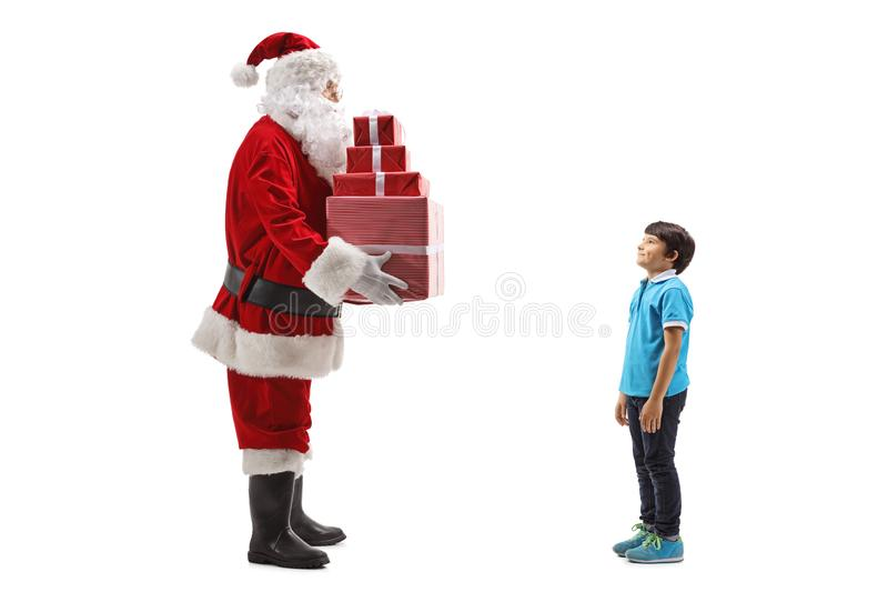 Santa Claus giving a pile of presents to a boy stock image