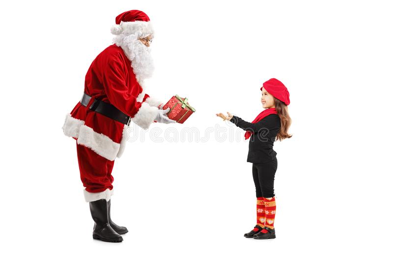 Santa Claus giving a present to a little girl royalty free stock photo