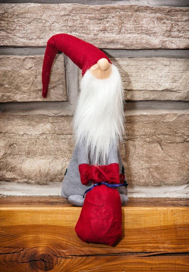 Santa Claus gjorde av torkduken med gåvor sitter över stenen f arkivbild