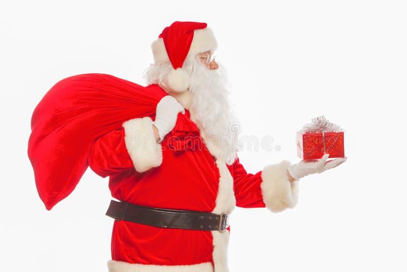 Santa Claus: Gladlynt med den lilla bunten av den stora påsen för gåvor, isolat arkivfoton