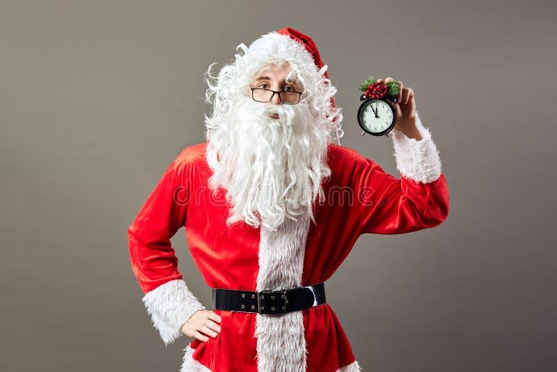 Santa Claus in glazen houdt klok een klok die vijf tot twaalf in zijn hand op de grijze achtergrond toont royalty-vrije stock foto's
