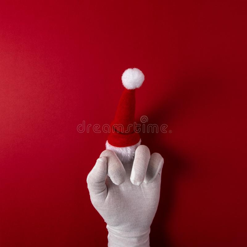 Santa Claus gloved hand is showing middle finger on red background. Christmas or New Year minimal concept stock photo