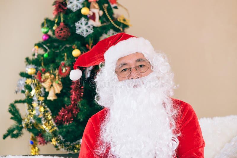Santa Claus gloved handen die giftdoos in ruimte houden Santa Claus gebrachte giften voor Kerstmis en het hebben van een rust doo stock afbeelding