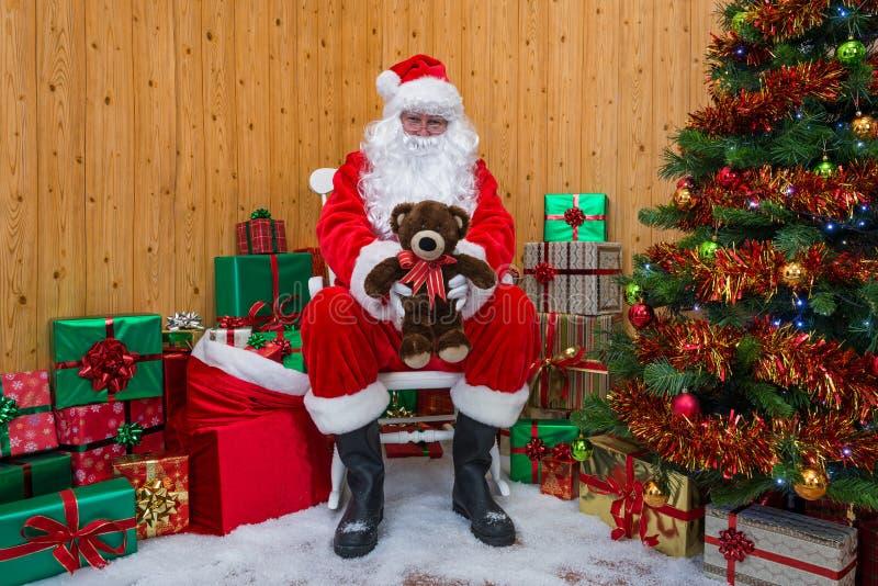 Santa Claus in a grotto giving you a teddy bear. royalty free stock photos