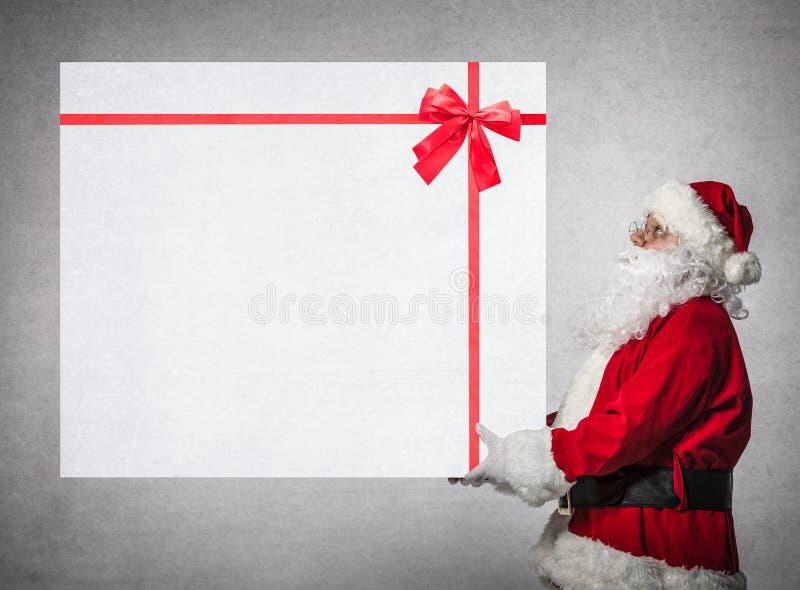 Santa Claus guarda a caixa de presente grande foto de stock royalty free