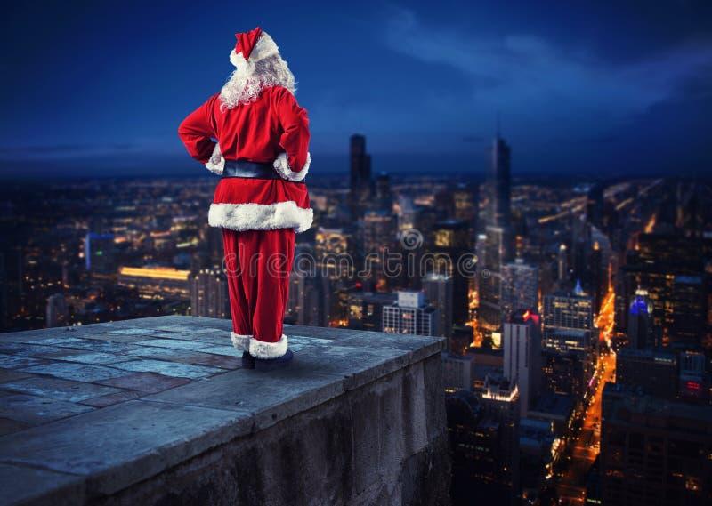 Santa Claus guarda dall'alto in basso la città che aspetta per consegnare i presente immagini stock libere da diritti