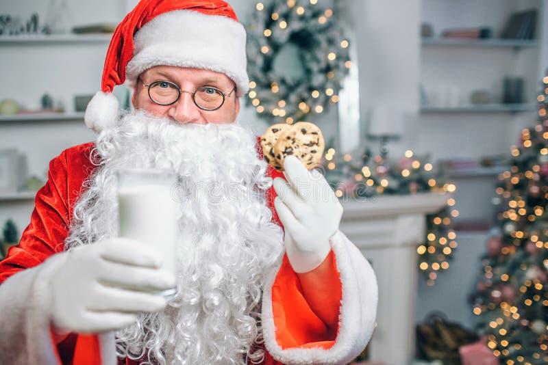 Santa Claus hält Glas Milch und zwei Plätzchen in den Händen Er bietet es an Mann schaut auf Kamera stockfotos