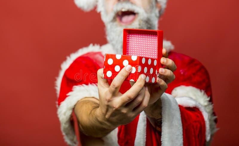 Santa Claus händer som rymmer giftbox Stilig man som kläs som lyckliga Santa Claus och att le Uppsökte Santa Claus med länge fotografering för bildbyråer