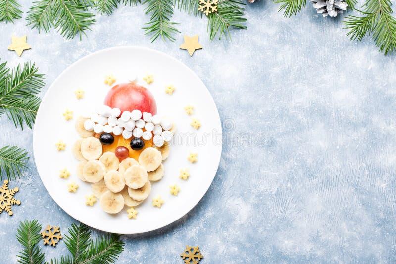 Santa Claus hace frente hecho de frutas y de la melcocha en una placa Comida de la Navidad para los niños Visión superior fotos de archivo