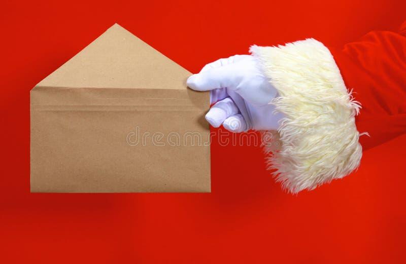 Santa Claus-Hand, die Ihren Weihnachtstext oder -produkt über rotem Hintergrund mit Kopienraum darstellt lizenzfreies stockbild