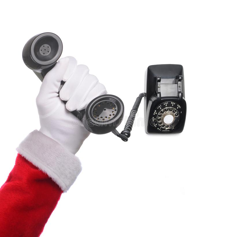 Santa Claus hand holding and antique rotary dial telephone isolated over white background. With receiver close to camera and base toward background. Square royalty free stock image