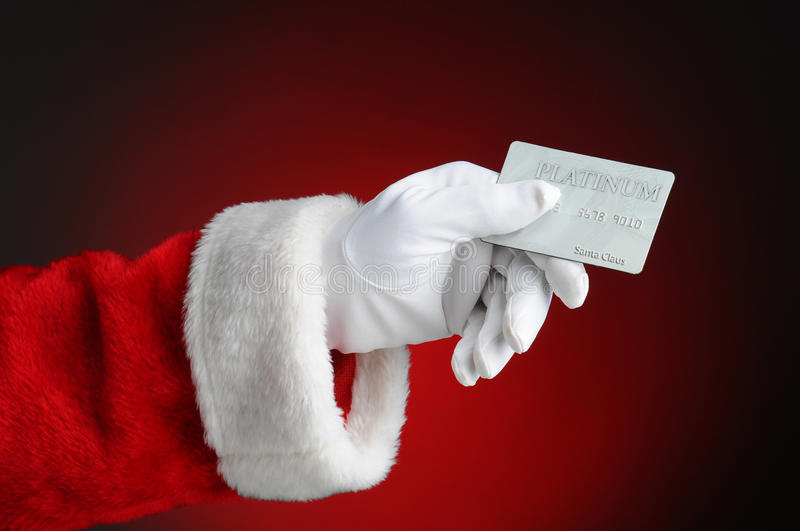Santa Claus Hand Holding Credit Card. Closeup of Santa Claus hand holding a Platinum Credit Card. Horizontal format over a light to dark red background royalty free stock photo