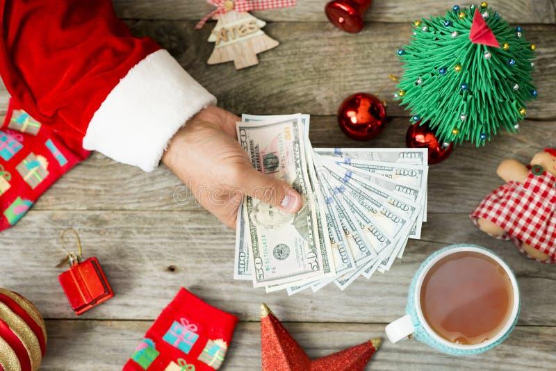 Santa Claus hand som rymmer kassapengar mot julbakgrund som föreslår höga kostnader under ferierna arkivbilder
