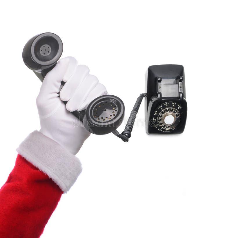 Santa Claus-Handholding und antikes Drehskalatelefon lokalisiert über weißem Hintergrund lizenzfreies stockbild