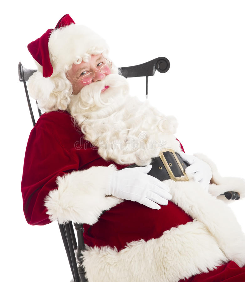 Santa Claus With Hands On Stomach que senta-se na cadeira imagem de stock royalty free