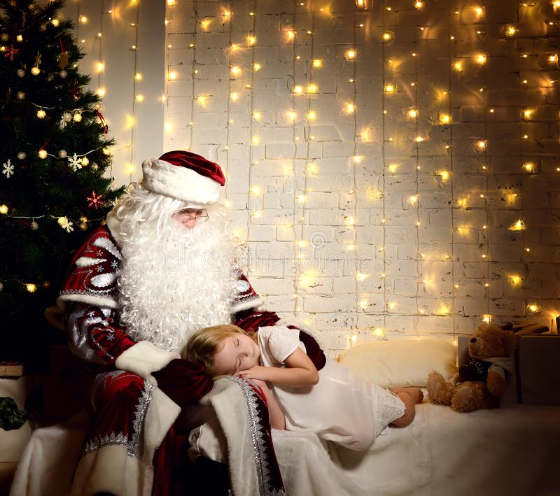 Santa Claus with happy little cute baby girl near Christmas tree royalty free stock photography
