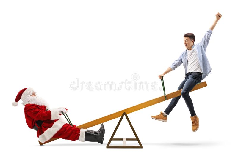 Santa Claus and a happy male teenager playing on a seesaw stock photos