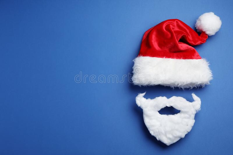 Santa Claus hat and beard on blue background, flat lay. Space for text stock photo