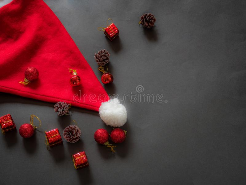Santa Claus hat on black with christmas decoration and copy space royalty free stock photography