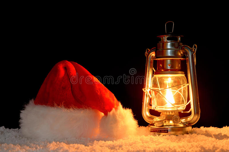 Santa Claus hat and lantern on snow royalty free stock image