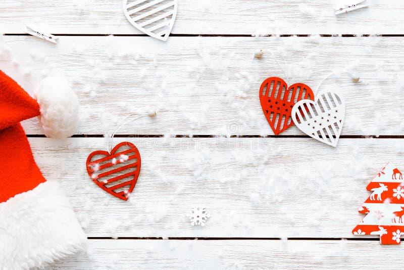Santa Claus hatt, röda hjärtor på trävit bakgrund, för valentindag för glad jul kort, lyckligt nytt år, bästa sikt royaltyfri foto