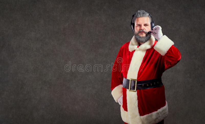 Santa Claus in a headset call center operator. Santa Claus in a headset call center operator on a copyspace background stock image