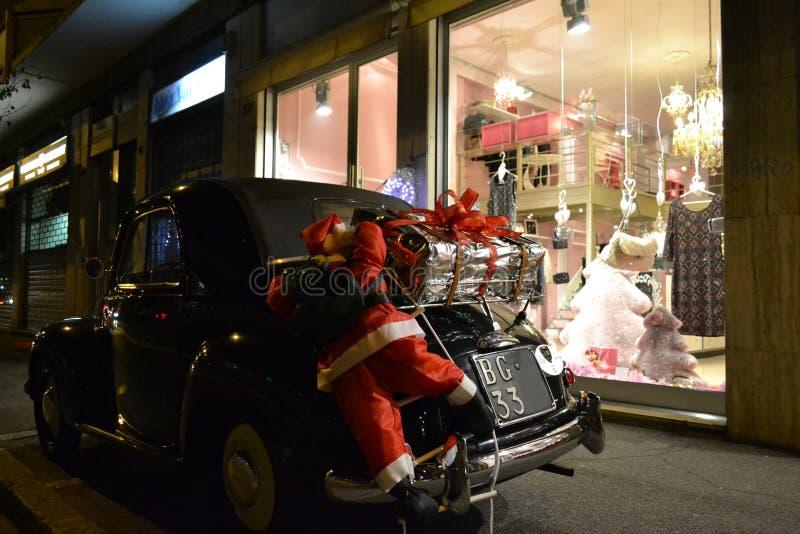 Santa Claus-het model is in bijlage aan de uitstekende zwarte auto van FIAT500 met giften royalty-vrije stock fotografie