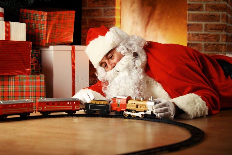 Santa Claus-het spelen met speelgoed onder de Kerstboom stock afbeeldingen