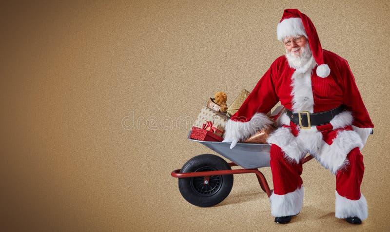 Santa Claus heureuse avec une brouette complètement des cadeaux de Noël sur un fond simple avec l'espace de copie photo stock