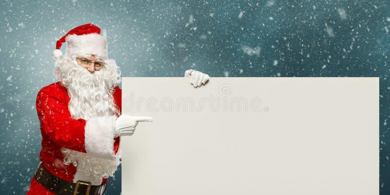 Santa Claus heureuse indique une bannière vide avec à l'espace de copie image libre de droits