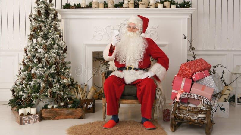 Santa Claus heureuse lisant des messages de Noël au téléphone et souriant tout en se reposant à sa chaise image libre de droits