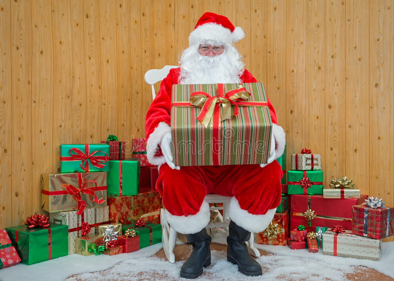 Santa Claus in his grotto holding a gift wrapped present stock photography
