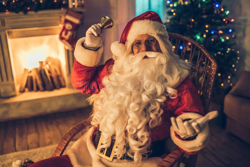 Santa Claus in his residence. Happy Santa Claus in eyeglasses is preparing to Christmas in his residence, sitting in rocking chair, smiling and looking at camera stock photo