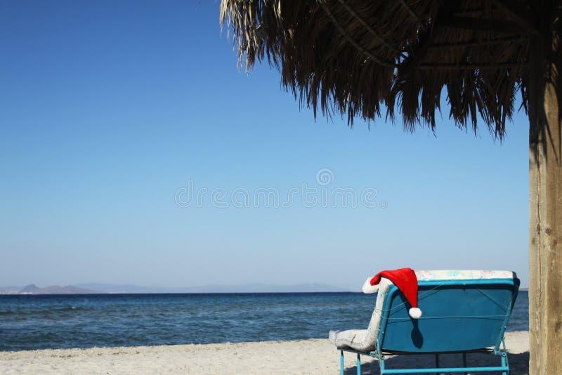 Santa Claus-hoed sunbed op strand onder zonnescherm stock afbeeldingen