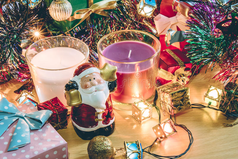 Santa claus hold bell, white and violet christmas candle, Ornament decorate Merry Christmas and happy new year. White and Violet Candle, ornament and christmas stock photo