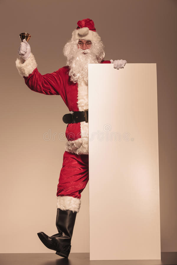 Santa Claus holding a bell and a blank billboard royalty free stock image