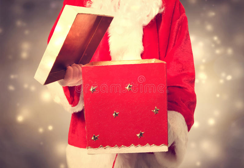Santa Claus Holding ed aprire un grande regalo di Natale fotografia stock