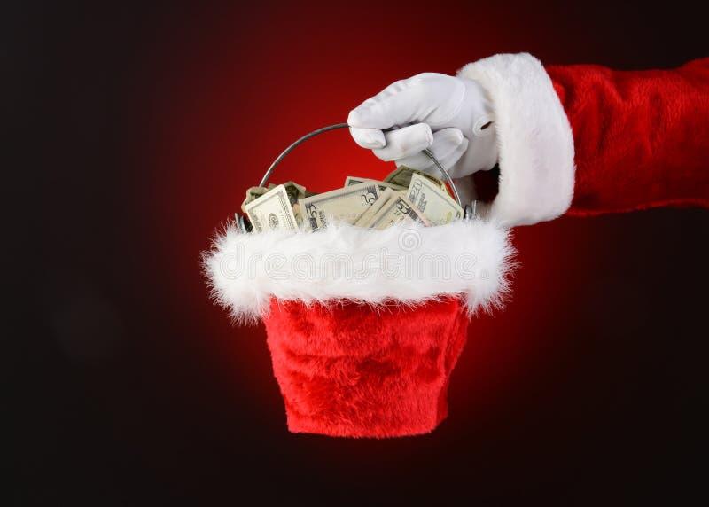 Santa Claus Holding en hink av kassa royaltyfri foto
