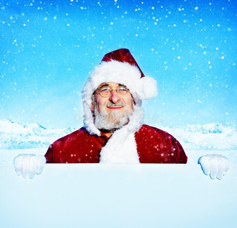 Santa Claus Holding ett tomt tecken som snöar begrepp fotografering för bildbyråer