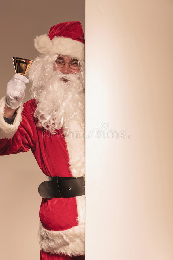 Santa Claus holding a golden bell in his hand royalty free stock photography