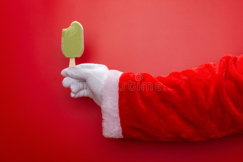 Santa claus holding green bean popsicle with a bite in front of a red background royalty free stock images