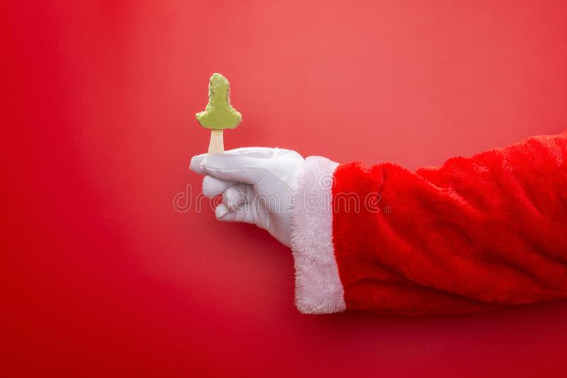 Santa claus holding green bean popsicle with the last bit in front of a red background royalty free stock images