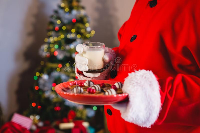 Santa Claus holding plate of sweet food with glass of milk. At home stock photography