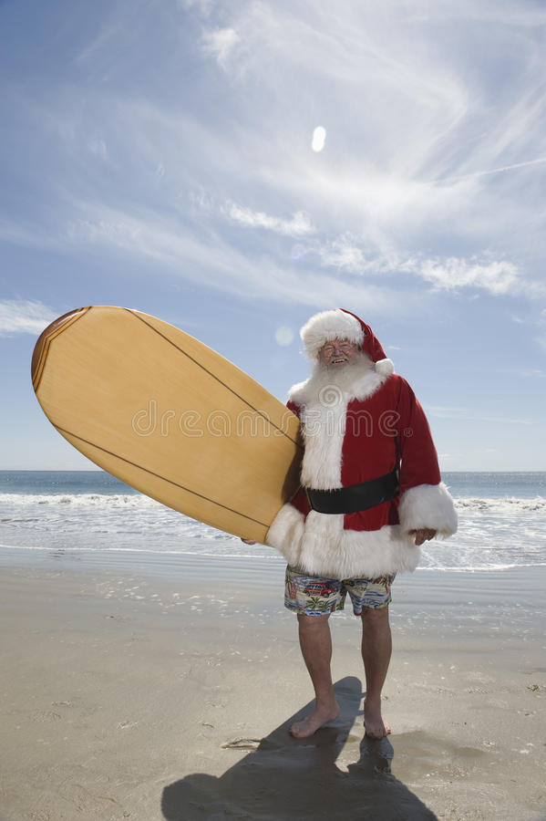 Santa Claus Holding Surfboard On Beach stock foto