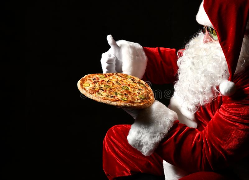 Santa Claus is holding tasty pizza on his open palm, showing thumb up, looking at it. New year and Merry Christmas. Santa Claus in stylish sunglasses is holding royalty free stock images
