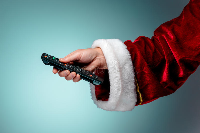 Santa Claus holding tv remote control royalty free stock photo