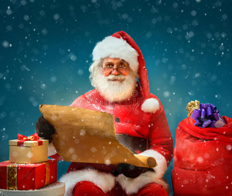 Santa Claus holding vintage paper and reads long list of gifts for children. Merry Christmas & New Year's Eve concept royalty free stock photography